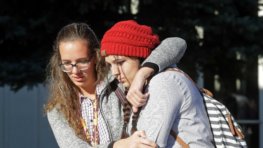 Students Albany Cox, right, and Holly Hilton leave Mountain View High School where several students were stabbed Tuesday.
