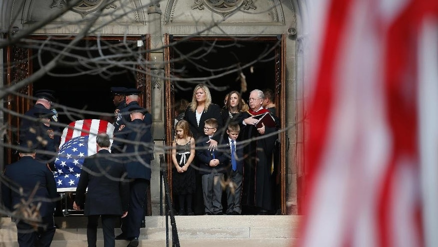 The family of slain Canonsburg Police officer Scott Bashioum, right, watches as the casket is carried up the steps into the Church of the Covenant for his funeral in Washington, Pa., Wednesday, Nov. 16, 2016. Bashioum was killed and a fellow officer wounded answering a Nov. 10 domestic dispute call. Authorities said 47-year-old Michael Cwiklinski shot both after killing 28-year-old Dalia Sabae. (AP Photo/Jared Wickerham)