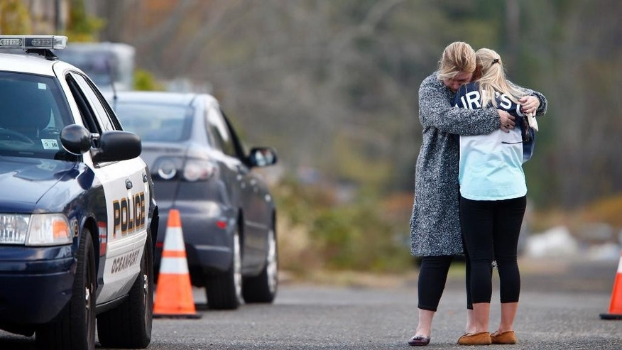 ADDS TO CLARIFY THE REPORT IN CAPTION - A woman, who police identified as a friend of the victim, is consoled by another woman on the long driveway that leads to the rear of Foggia Florist in Oceanport, N.J., Wednesday, Nov. 16, 2016. Police believe a body discovered in the New Jersey city is that of a Connecticut man who went missing after attending a party at a luxury apartment building in New York City over the weekend. Joseph Comunale, of Stamford, Conn., was last seen entering the Grand Sutton building in Manhattan on Sunday morning. (Thomas P. Costello/The Asbury Park Press via AP)