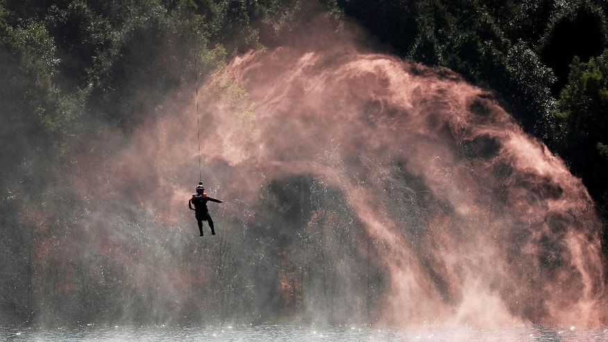 A soldier is lowered from a helicopter to practice rescuing a person in the water during a joint rescue operation in the U.S.-China Disaster Management Exchange (DME) in Kunming, China's Yunnan Province, Friday, Nov. 18, 2016. Hundreds soldiers from Chinese PLA Southern Theater Command Army and the U.S. Army Pacific conducted the fourth round of Disaster Management Exchange (DME) joint drill held in southwestern China's Yunnan province on Friday, as part of the exchanges between the two countries' militaries. (AP Photo/Andy Wong)