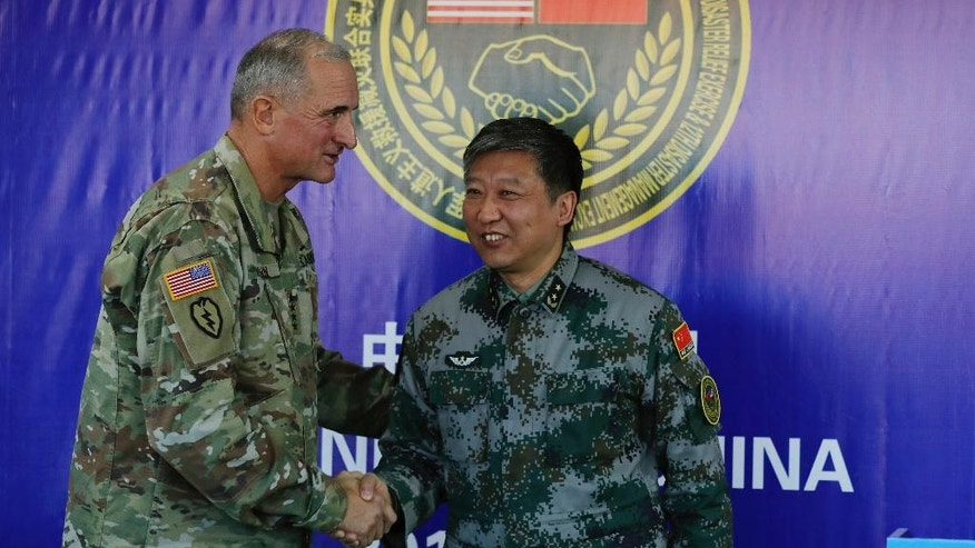U.S. Army Pacific commander Gen. Robert Brown, left, shakes hands with Gen. Liu Xiaowu, the commander for Southern Theater Command Army of Chinese Liberation Army (PLA) at the end of their joint press conference after conducting U.S.-China joint drills at a PLA's training base in Kunming in southwest China's Yunnan province, Friday, Nov. 18, 2016. Chinese and U.S. troops staged U.S.-China Disaster Management Exchange joint drills Friday in an effort to better coordinate a response to humanitarian disasters and build confidence between their militaries that remain deeply wary of each other. (AP Photo/Andy Wong)