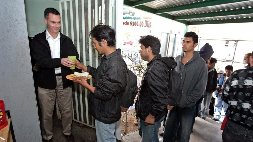 FILE - In this March 9, 2009 file photo, Rev. Sean Carroll, left, executive director of the Kino Border Initiative, hands out food at the Aid Center for Deported Migrants in Nogales, Mexico. The dangers faced by migrants often extend to the shelters who try to help them. During a recent break-in, vandals left feces on crosses made by migrant men. Someone made a threatening call Carroll. Migrant shelters along the border face such dangers on a daily basis, although some say they haven't seen any incidents recently. (AP Photo/Arizona Daily Star, Benjie Sanders, File)