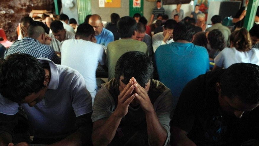 FILE - In this July 29, 2010 file photo, deportees pray as they gather for breakfast provided by the Kino Border Initiative in Nogales, Sonora, Mexico. The dangers faced by migrants often extend to the shelters who try to help them. During a recent shelter break-in, vandals left feces on crosses made by migrant men. Someone made a threatening call to a minister. Migrant shelters along the border face such dangers on a daily basis, although some say they haven't seen any incidents recently. (AP Photo/Jae C. Hong, File)