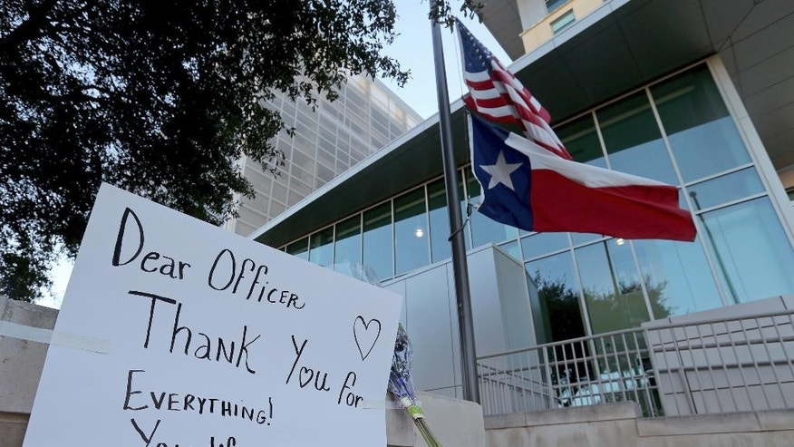 An American flag and a Texas state flag fly at half-staff at San Antonio Police Department headquarters near a sign and flowers left by Lucy Aldaba after Det. Benjamin Marconi was fatally shot Sunday, Nov. 20, 2016, in San Antonio. Marconi was writing out a traffic ticket to a motorist when he was shot to death in his squad car Sunday outside police headquarters by another driver who pulled up from behind, authorities said. (Edward A. Ornelas/The San Antonio Express-News via AP)