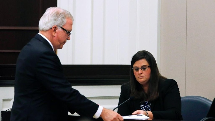 Defense attorney Andy Savage hands documents to State Law Enforcement Division trace evidence examiner Megan Fletcher as she testifies in the murder trial of former North Charleston police officer Michael Slager at the Charleston County court in Charleston, S.C., Monday, Nov. 21, 2016. Slager is charged in the April 2015 shooting death of 50-year-old Walter Scott as Scott fled from a traffic stop. (Grace Beahm/Post and Courier via AP, Pool)
