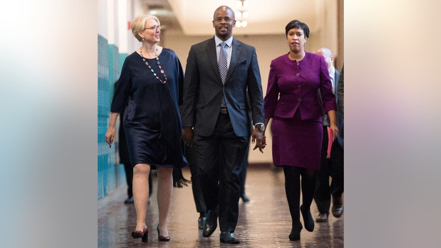 From left, Washington Deputy Mayor for Education Jennifer Niles, incoming Washington Schools Chancellor Antwan Wilson, and Washington Mayor Muriel Bowser arrive for a news conference at Easter High School in Washington, Tuesday, Nov. 22, 2016, to announce Wilson in his new role. (AP Photo/Andrew Harnik)
