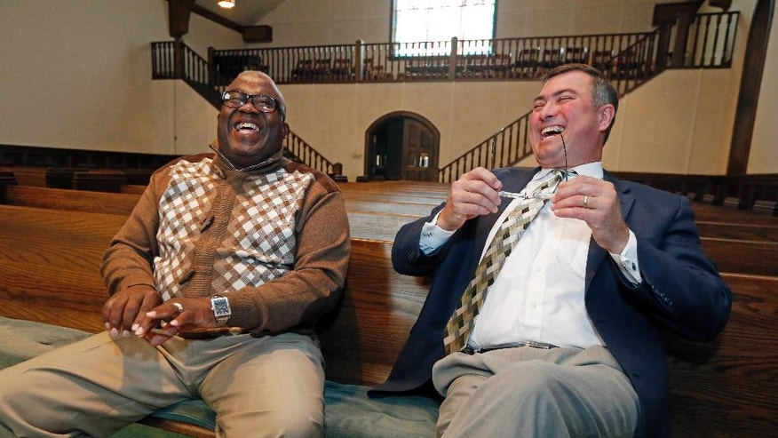 "Bishop Clarence Green, overseer of Hopewell Missionary Baptist Church, left, and Pastor James Nichols of the First Baptist Church of Greenville laugh together  inside the chapel that First Baptist offered as a temporary home for the members of Hopewell, Tuesday, Nov 22, 2016, in Greenville, Miss. Hopewell was burned three weeks ago and spray-painted with ""Vote Trump."" An investigation into the cause of the fire continues. (AP Photo/Rogelio V. Solis)"