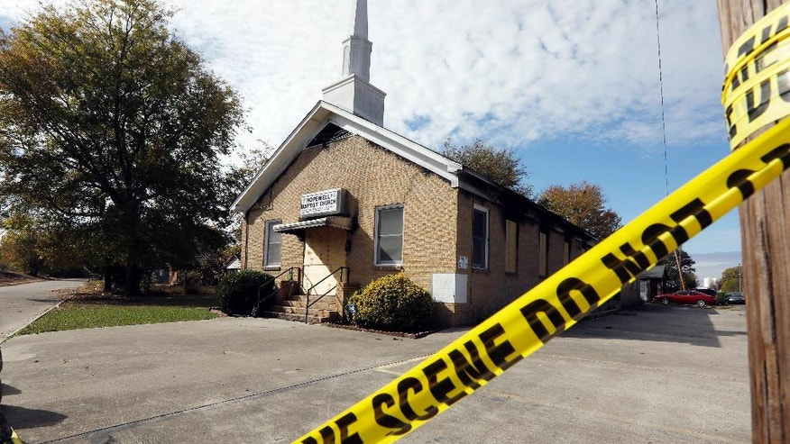 "Crime scene tape outlines the perimeter of the Hopewell Missionary Baptist Church in Greenville, Miss., on Tuesday, Nov. 22, 2016, after the church was burned and spray-painted with ""Vote Trump,"" three weeks ago. The First Baptist Church of Greenville has offered congregants of the burned church a new place to worship.  (AP Photo/Rogelio V. Solis)"
