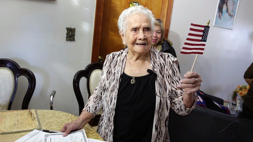 America Maria Hernandez, 99, holds an American flag after being administered the Naturalization Oath of Allegiance, Wednesday, Nov. 23, 2016 photo, in the Queens borough of New York. The Colombian immigrant, who was brought to the U.S. by one of her daughters in 1988, signed her naturalization certificate and took the oath of allegiance in her living room, surrounded by family members and TV cameras. (AP Photo/Richard Drew)