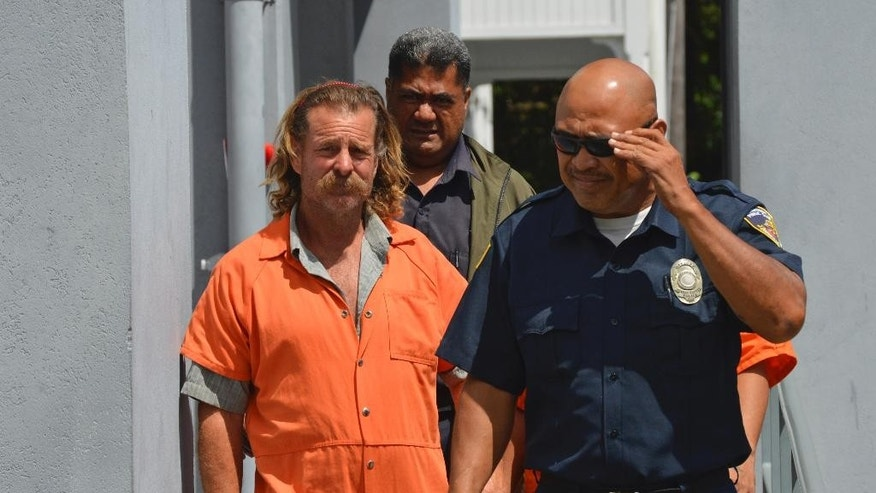 In this Oct. 4, 2016 photo provided by the Samoa News, Dean Fletcher, left, is escorted by a police officer after his initial appearance in the District Court of American Samoa in Pago Pago, American Samoa. Tonga officials told U.S. prosecutors that Dean Fletcher was indicted on murder in the July death of his wife, Patricia Linne Kearney. Court documents say witnesses saw Fletcher assaulting Kearney on a dinghy. The next day, Fletcher told police his wife fell down stairs of their yacht. (Ausage Fausia/Samoa News via AP)