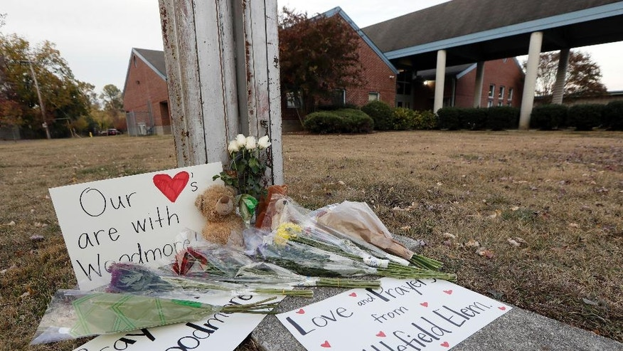 Flowers, signs and stuffed animals make up a makeshift memorial outside Woodmore Elementary School on Tuesday, Nov. 22, 2016, in Chattanooga, Tenn. The school bus driven by Johnthony Walker, 24, crashed while transporting children home from the school Monday, killing at least five students. Walker was arrested Monday and charged with five counts of vehicular homicide including reckless driving and reckless endangerment, police said. (AP Photo/Mark Humphrey)