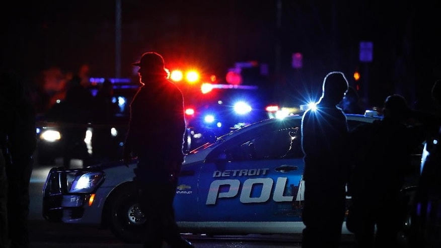 "Police search the area where an officer who works for Wayne State University was shot in the head while on duty near the campus Tuesday, Nov. 22, 2016, in Detroit. Authorities said they have a ""person of interest"" in custody in the investigation into the shooting of the police officer. (AP Photo/Paul Sancya)"