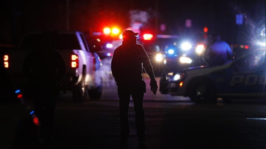 "Police search the area where a police officer who works for Wayne State University was shot in the head while on duty near the campus Tuesday, Nov. 22, 2016, in Detroit. Authorities said they have a ""person of interest"" in custody in the investigation into the shooting of the police officer. (AP Photo/Paul Sancya)"