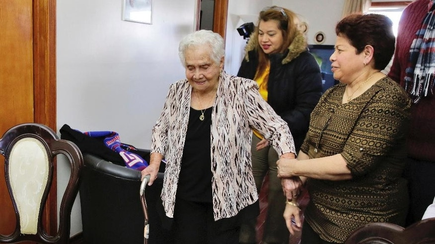 America Maria Hernandez, 99, left, is aided by her granddaughter Monica Martinez, center, and daughter Ana Martinez as she prepares to take the Naturalization Oath of Allegiance, Wednesday, Nov. 23, 2016, in the Queens borough of New York. The Colombian immigrant, who was brought to the U.S. by one of her daughters in 1988, signed her naturalization certificate and took the oath of allegiance in her living room, surrounded by family members and TV cameras.  (AP Photo/Richard Drew)