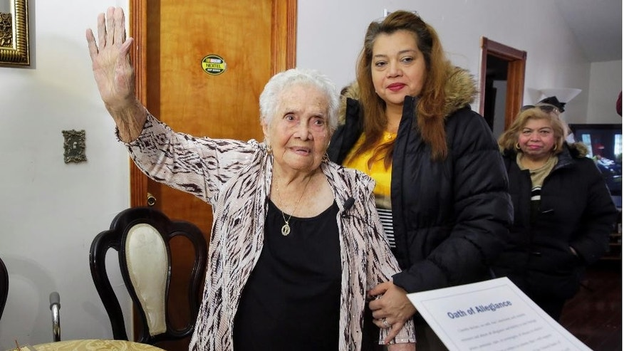 In this Nov. 23, 2016 photo, America Maria Hernandez, 99, left, is joined by her granddaughter Monica Martinez, center, and daughter Hortensia Martinez as she is administered the Naturalization Oath of Allegiance, in the Queens borough of New York. The Colombian immigrant, who was brought to the U.S. by one of her daughters in 1988, signed her naturalization certificate and took the oath of allegiance in her living room, surrounded by family members and TV cameras. (AP Photo/Richard Drew)