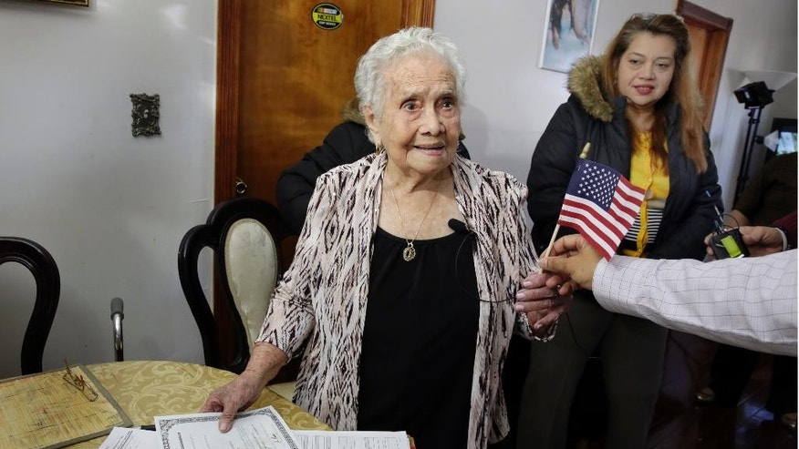 America Maria Hernandez, 99, receives an American flag after being administered the Naturalization Oath of Allegiance, Wednesday, Nov. 23, 2016, in the Queens borough of New York.  The Colombian immigrant, who was brought to the U.S. by one of her daughters in 1988, signed her naturalization certificate and took the oath of allegiance in her living room, surrounded by family members and TV cameras. Looking on at right is her granddaughter Monica Martinez. (AP Photo/Richard Drew)