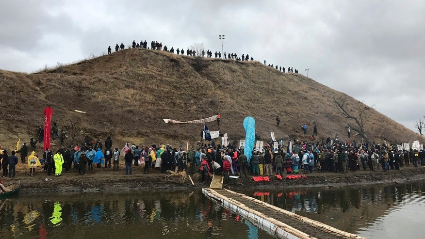 In this photo provided by Nancy Trevino, protesters against the Dakota Access oil pipeline gather at and around a hill, referred to as Turtle Island, where demonstrators claim burial sites are located, Thursday, Nov. 24, 2016 in Cannon Ball, N.D.