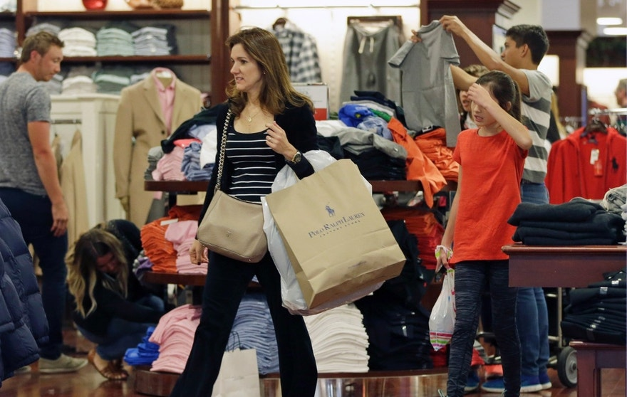 A shopper carries a bag with merchandise as she shops at a Polo Ralph Lauren store on Black Friday, Nov. 25, 2016, in Miami. Stores open their doors Friday for what is still one of the busiest days of the year, even as the start of the holiday season edges ever earlier. (AP Photo/Alan Diaz)
