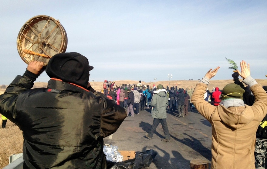 Protesters against the Dakota Access oil pipeline congregate Monday, Nov. 21, 2016, near Cannon Ball, N.D., on a long-closed bridge on a state highway near their camp in southern North Dakota. The bridge was the site of the latest skirmish between protesters and law officers, in which officers used tear gas, rubber bullets and pepper spray, and authorities say protesters assaulted officers with rocks and burning logs. (AP Photo/James MacPherson)