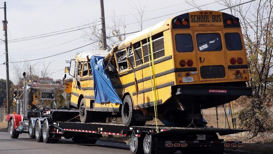 FILE- In this Nov. 22, 2016, file photo, a school bus is carried away in Chattanooga, Tenn., from the site where it crashed. Students and administrators raised concerns about a Tennessee school bus driver's behavior behind the wheel in the weeks before a crash that killed several children. Records released by the school district Friday, Nov. 25, include two written statements by students complaining about Johnthony Walker's driving. (AP Photo/Mark Humphrey, File)