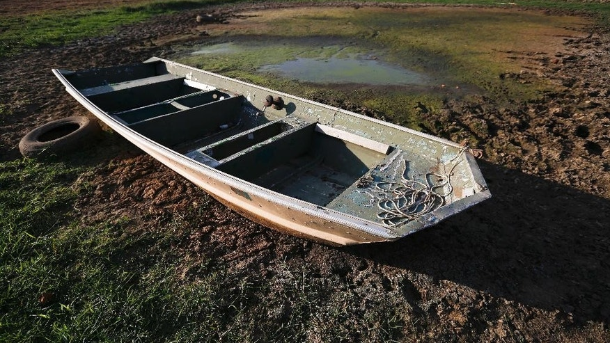 FILE - In this Wednesday, Oct. 26, 2016 file photo, an abandoned boat sits in the remains of a dried out pond in Dawson, Ala. Though water shortages have yet to drastically change most people's lifestyles, southerners are beginning to realize that they'll need to save their drinking supplies with no end in sight to an eight-month drought. Already, watering lawns and washing cars is restricted in some parts of the South, and more severe water limits loom if long-range forecasts of below-normal rain hold true through the rest of 2016. (AP Photo/Brynn Anderson, File)