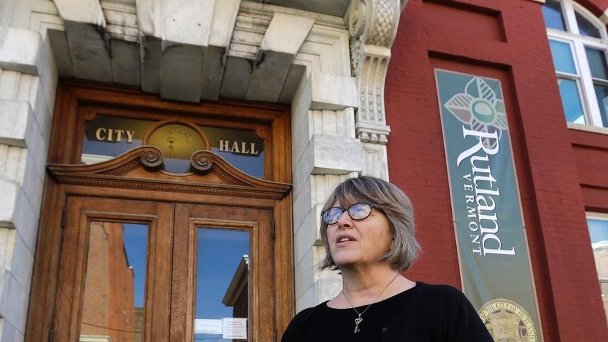 In this Nov. 14, 2016 photo, Rutland City Treasurer Wendy Wilton speaks outside city hall in Rutland, Vt. After months of bitter debate, the down-on-its heels city is preparing to start accepting up to 100 Syrian refugees. (AP Photo/Elise Amendola)