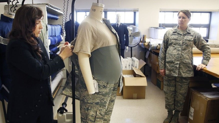 Air Force Uniform Office clothing designer Stacey Butler, left, adjusts an improved maternity uniform prototype on a mannequin that is also being tested by a pregnant Capt. Mollie Eshel.