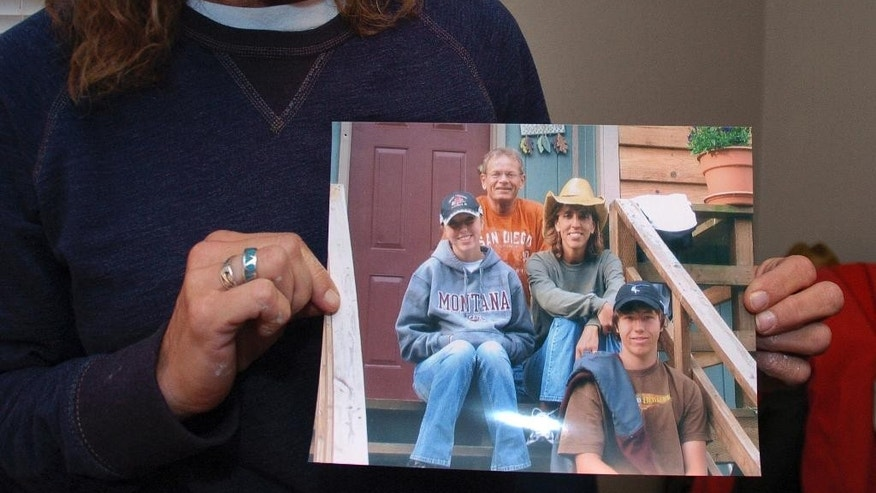 FILE - In this Nov. 5, 2013 file photo, Rhonda Whited-Rupp holds a picture of her sister, Sherry Arnold, seen in a cowboy hat, and Arnold's family in Sidney, Mont. A defense attorney says Michael Keith Spell, a mentally-disabled Colorado man serving a 100-year prison term for Arnold's murder, should be transferred to the custody of state mental health officials. Attorney Wendy Holton said in an appeal brief filed Tuesday, Nov. 29, 2016 that Spell needs treatment that he won't receive in prison. Spell's 2012 killing of Arnold in the once-quiet town of Sidney highlighted a significant spike in crime following an oil boom that's swept the Northern Plains. (AP Photo/Matthew Brown, File)