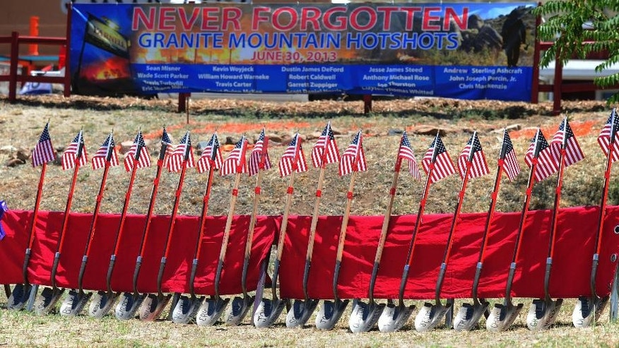 FILE - In this June 28, 2015, file photo, flag-topped shovels with the names of the Granite Mountain Hotshots on their blade were a grim reminder of the loss of life that occurred two years ago as local residents gather for the Remembrance Event of the 2nd Anniversary of the Yarnell Hill Fire in Yarnell, Ariz. Arizona Gov. Doug Ducey plans to dedicate a long-awaited memorial for the 19 Granite Mountain Hotshots who perished in a wildfire three years ago. Ducey will be joined by family members of the fallen firefighters on Tuesday, Nov. 29, 2016, at a private dedication of the Granite Mountain Hotshots Memorial State Park. (Les Stukenberg/The Daily Courier via AP, File)