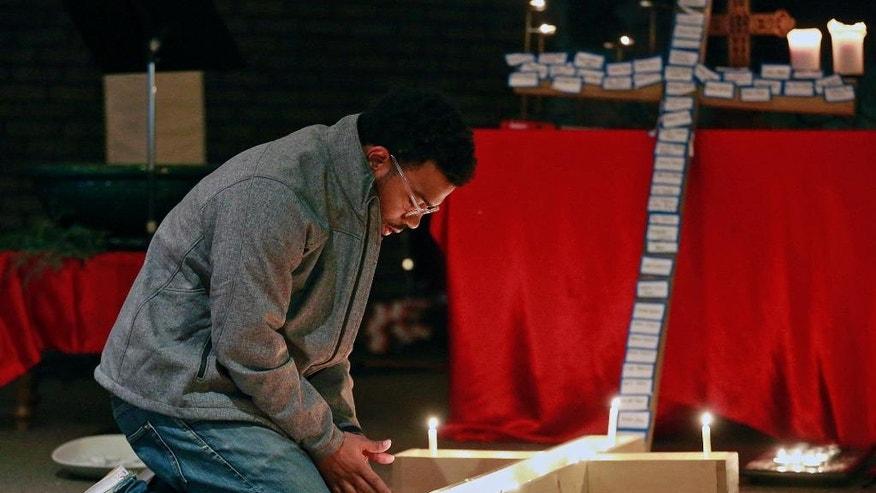 A student lights a candle inside a cross during a vigil at Jacob's Porch, the Lutheran Campus Ministry at Ohio State University in Columbus, Ohio, Monday, Nov. 28, 2016. A Somali-born Ohio State University student plowed his car into a group of pedestrians on campus and then got out and began stabbing people with a butcher knife Monday before he was shot to death by a police officer. (Barbara J. Perenic/The Columbus Dispatch via AP)