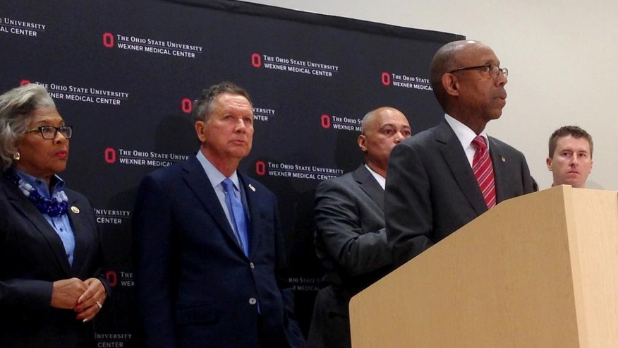 Ohio Gov. John Kasich, second from left, listens as Ohio State University President Michael Drake speaks during a news conference Monday, Nov. 28, 2016, in Columbus, Ohio. A Somali-born Ohio State University student plowed his car into a group of pedestrians on campus and then got out and began stabbing people with a knife Monday before he was shot to death by an officer. (AP Photo/Juile Smyth)