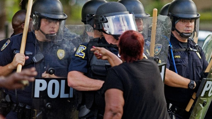 "FILE -In this July 9, 2016 file photo, a protester yells at police in front of the Baton Rouge Police Department headquarters after police arrived in riot gear to clear protesters from the street in Baton Rouge, La. A settlement agreement Tuesday, Nov. 29 resolves a federal lawsuit that accuses law enforcement of trampling on the civil rights of protesters in Baton Rouge following a black man's fatal shooting by police. Plaintiffs' attorneys said their ""memorandum of understanding"" with state and local police officials affirms that people have the right to peacefully protest. The agreement doesn't include any monetary terms.  (AP Photo/Max Becherer, File)"