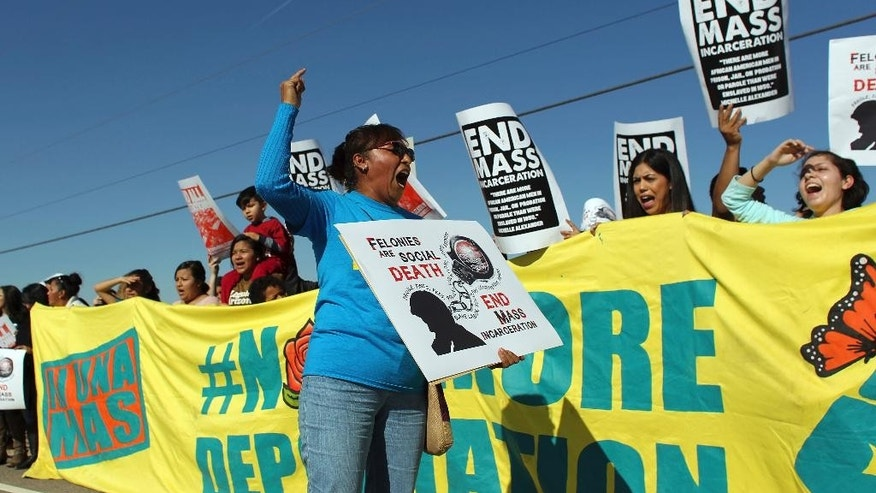 FILE - In this Jan. 20, 2016, file photo, demonstrators shout slogans in front of the Eloy Detention Center, in Eloy, Arizona. Immigrant advocates say the recent death of a 36-year-old woman in custody at the immigration detention facility in Arizona that's had the most deaths in the U.S. is another example of poor practices and inadequate care. (AP Photo/Ricardo Arduengo, File)