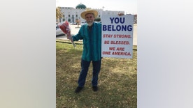 """In an undated photo provided by Justin Normand,, Normand holds a sign of support outside the Islamic Center of Irving, Texas. Normand says his """"You Belong"""" message was prompted by hatred directed at Muslims as part of the recent presidential election. (Justin Normand via AP)"""