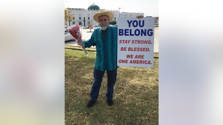 "In an undated photo provided by Justin Normand,, Normand holds a sign of support outside the Islamic Center of Irving, Texas. Normand says his ""You Belong"" message was prompted by hatred directed at Muslims as part of the recent presidential election. (Justin Normand via AP)"