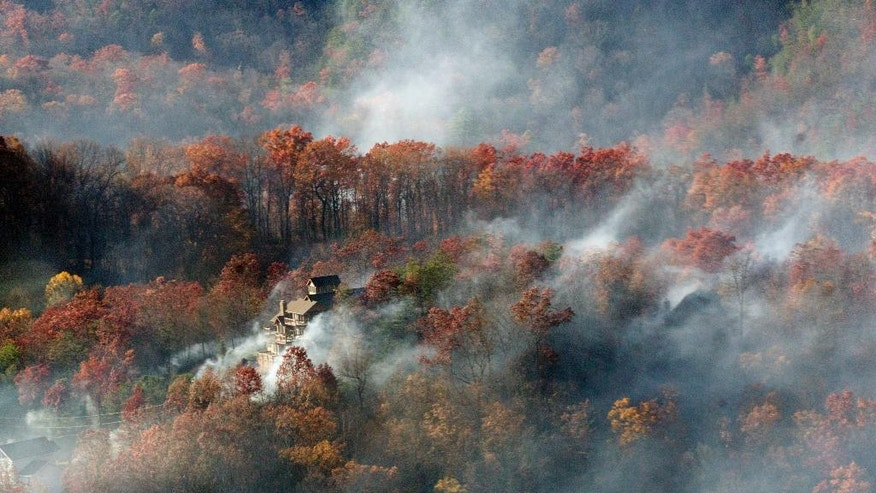 Smoke surrounds a home as seen from aboard a National Guard helicopter near Gatlinburg, Tenn., Tuesday, Nov. 29, 2016. Thousands of people have fled deadly wildfires that have destroyed hundreds of homes and a resort in the Great Smoky Mountains. (AP Photo/Erik Schelzig)