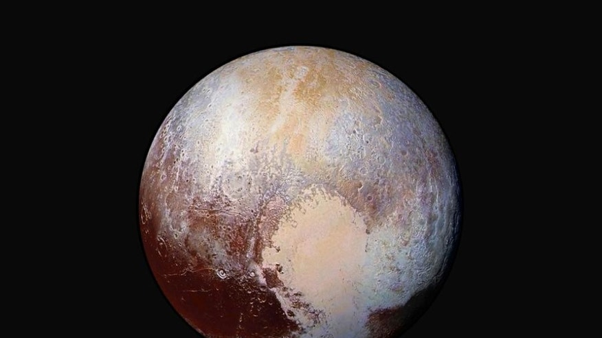 FILE - This image made available by NASA on July 24, 2015 shows a combination of images captured by the New Horizons spacecraft with enhanced colors to show differences in the composition and texture of Pluto's surface. The deep icy basin in Pluto's heart-shaped region may be a natural sinkhole. In a study published Wednesday, Nov. 30, 2016, a team led by University of Maryland astronomer Douglas Hamilton suggests the basin may have resulted from the weight of surface ice. (NASA/JHUAPL/SwRI via AP)