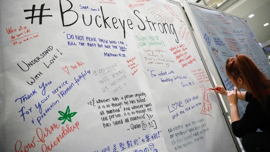 Student Ashley Greivenkamp signs a community message board at The Ohio State University student union Tuesday, Nov. 29, 2016, following an attack at on campus the previous day, in Columbus, Ohio. Investigators are looking into whether a car-and-knife attack at Ohio State University that injured several people was an act of terror by a student who had once criticized the media for its portrayal of Muslims. (AP Photo/John Minchillo)