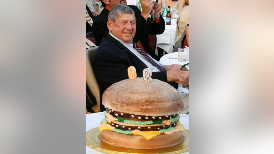 "FILE - In this Aug. 21, 2008, file photo, Big Mac creator Michael ""Jim"" Delligatti sits behind a Big Mac birthday cake at his 90th birthday party in Canonsburg, Pa. Delligatti, the Pittsburgh-area McDonald's franchisee who created the Big Mac in 1967, has died. He was 98. (AP Photo/Gene J. Puskar, File)"