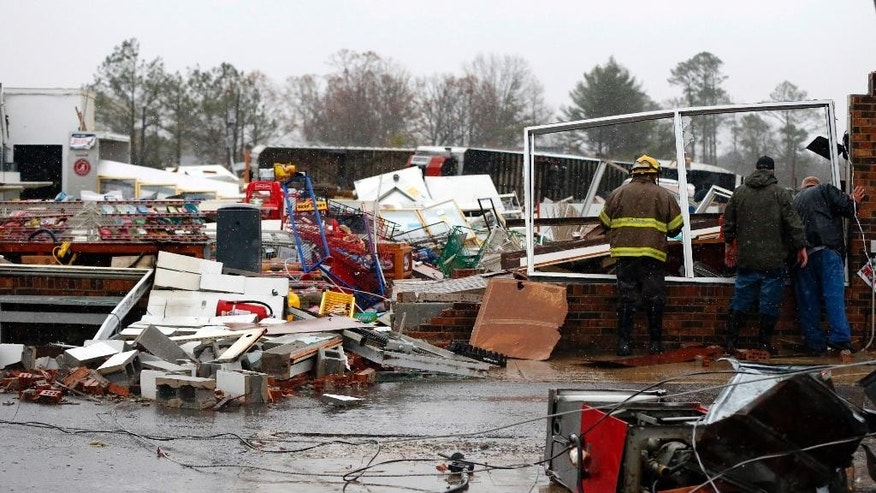 A Rosalie firefighter helps remove debris from the Rosalie Plaza after a tornado ripped through the town, Wednesday, Nov. 30, 2016, in Rosalie, Ala. Storms that spawned deadly winds have dumped more than 2 inches of rain across much of north Alabama, causing floods after months of drought.  (AP Photo/Butch Dill)