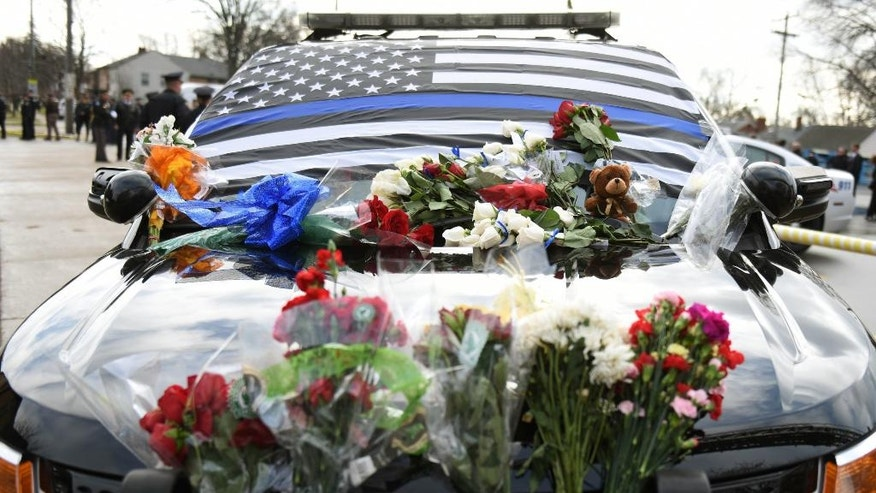 Fallen Wayne State University K-9 Police officer Collin Rose's police SUV is covered with flowers and mementos outside of Rose's funeral at St. Joan of Arc Catholic Church in St. Clair Shores, Mich., Thursday, Dec. 1, 2016. Rose was shot Nov. 22 as he tried to arrest DeAngelo Davis, who faces murder and gun charges.(Tanya Moutzalias  /The Ann Arbor News via AP)