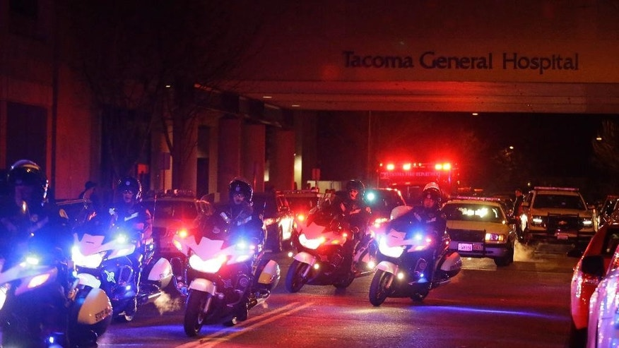 "Motorcycle law enforcement officers lead a procession away from Tacoma General Hospital of an ambulance bearing the body of a Tacoma Police officer who was shot and killed while answering a domestic violence call Wednesday, Nov. 30, 2016, in Tacoma, Wash. Tacoma Police spokeswoman Loretta Cool said the officer was pronounced dead at the hospital Wednesday evening. ""We've suffered a great loss and I think the community has suffered a great loss. I don't know how to put that into words,"" Cool said. (AP Photo/Ted S. Warren)"