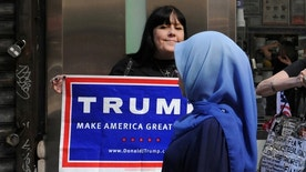 A woman wearing a Muslim headscarf walks past people holding U.S. Republican presidential nominee Donald Trump signs before the annual Muslim Day Parade in the Manhattan borough of New York City, September 25, 2016. REUTERS/Stephanie Keith/File Photo - RTX2PMXK
