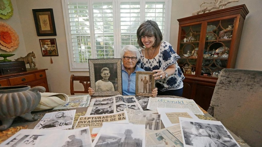 In this Tuesday, Nov. 22, 2016 photo, Frances R. Fuller, left, and her niece Kathrine Fuller, right, sister and niece respectively, of Robert Fuller, show photos of Fuller at their home in Miami. In 1960, Robert Fuller joined an ill-fated mission to lead a boatload of poorly trained Cubans from Miami in hopes of mustering up a counter-revolution on the island. Instead, the men were quickly captured, and Fuller confessed under torture to counterrevolutionary activities.  Fuller was sentenced to death by firing squad. The family asked to bring his body back with them to America. Castro's people said no. (AP Photo/Alan Diaz)