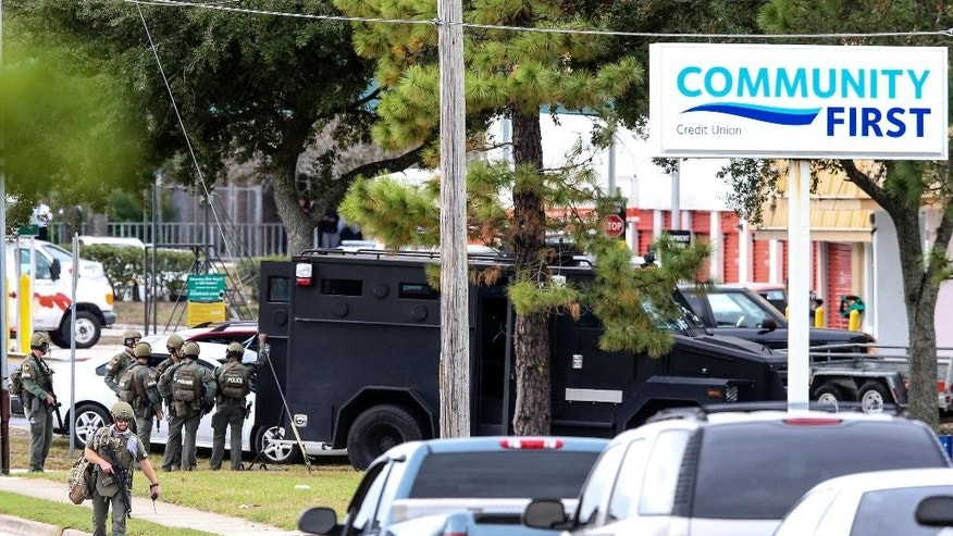 Law enforcement personnel gather near the Community First Credit Union bank, Thursday, Dec. 1, 2016, in Jacksonville, Fla., where authorities say a bank robber was holding several hostages. (AP Photo/Gary McCullough)