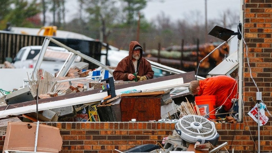 In this Nov. 30, 2016, photo, Gregg Jefferey, left, and his son Tyler help a family friend clean up their business at Rosalie Plaza after a possible tornado ripped through the town in Rosalie, Ala. The most extreme tornado outbreaks, like the deadly one Tuesday in the Southeast, are mysteriously spawning many more twisters than they did decades ago, a new study claimed. The same type of once-every-five-years-or-so outbreak that 50 years ago had about 12 tornadoes, now has on average about 20, said Columbia University applied physics professor Michael Tippett, lead author of the study in Thursday's journal Science.  (AP Photo/Butch Dill)