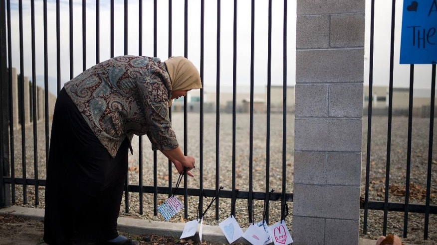 FILE - In this Dec. 4, 2015 file photo, Kareema Abdul-Khabir, who teaches special needs students at an elementary school in Barstow, Calif., places some cards made by her students at a makeshift memorial honoring the victims of a shooting rampage, in San Bernardino, Calif. In Dec. 2015, San Bernardino County health inspector Syed Farook and his Pakistan-born wife Tashfeen Malik opened fire on a meeting of Farook's colleagues, and were killed in a shootout with police. In the aftermath of the terror attack in San Bernardino, Muslims in this Southern California community feared a prolonged, hate-filled backlash. While there were some incidents, for the most part, their worst fears never happened. (AP Photo/Jae C. Hong, File)