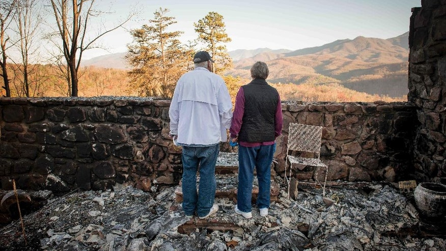 Richard T. Ramsey and Sue Ramsey hold hands while looking at the skyline from the remains of their house of 41 years, Thursday, Dec. 1, 2016, in Gatlinburg, Tenn. They safely evacuated from their home as wildfire approached Monday evening. (Andrew Nelles/The Tennessean via AP)
