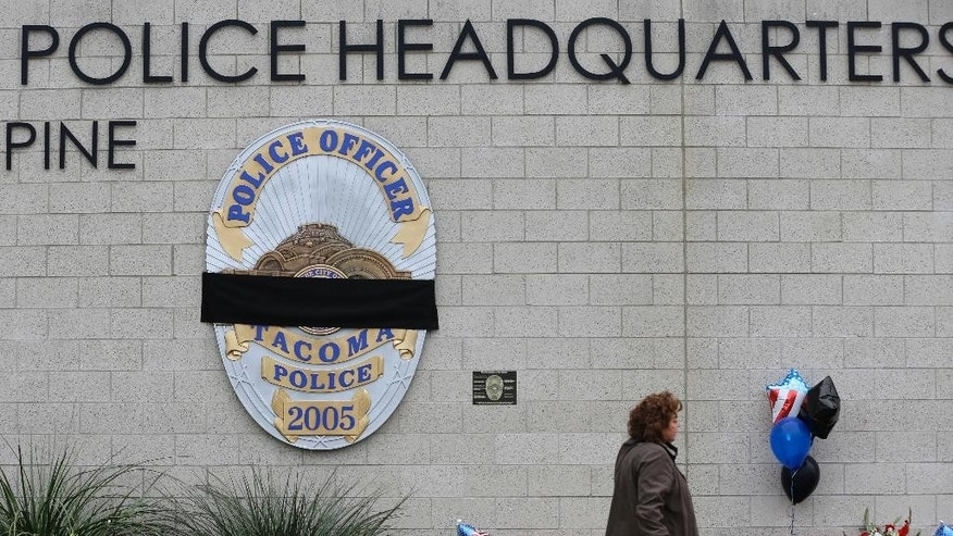 "A visitor walks past the growing memorial at Tacoma Police Headquarters, Thursday, Dec. 1, 2016, in memory of Tacoma Police Officer Reginald ""Jake"" Gutierrez. Gutierrez was shot while responding to a domestic violence call Wednesday and died later in the day at a hospital. (AP Photo/Ted S. Warren)"