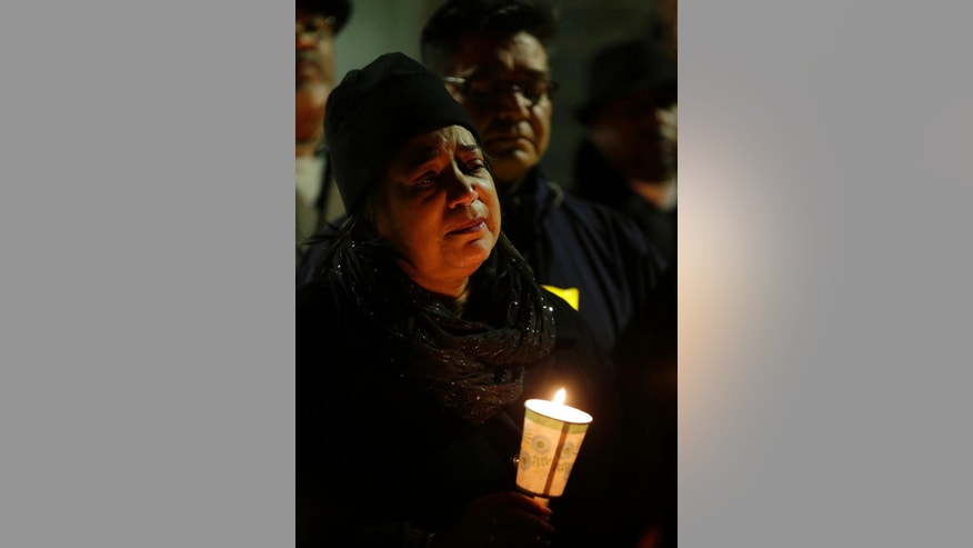 "Tacoma City Councilmember Victoria Woodards holds a candle as she attends a vigil Thursday, Dec. 1, 2016, for fallen Tacoma Police Officer Reginald ""Jake"" Gutierrez. Gutierrez was shot while responding to a domestic violence call Wednesday and died later in the day at a hospital. (AP Photo/Ted S. Warren)"